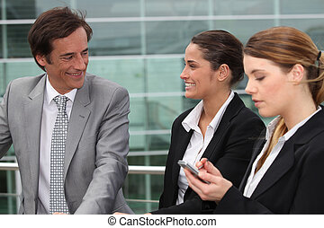 Three business people stood outside workplace