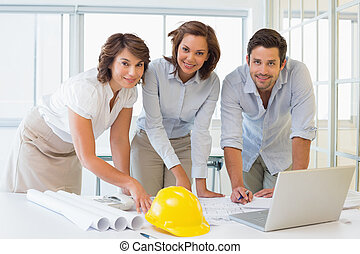 Three business people working on blueprints in office