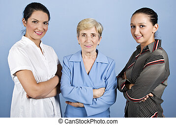 Three business women standing in a line with arms crossed...