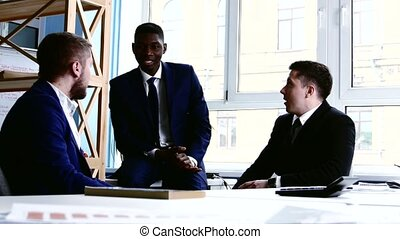 Three businessman vividly discussing something among themselves during the coffee break