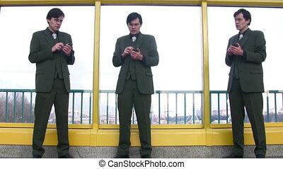 three businessmen clones with pocket pc - Three businessmen...