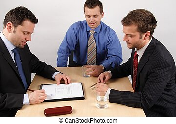 Three businessmen sitting at a table negotiating and signing a contract