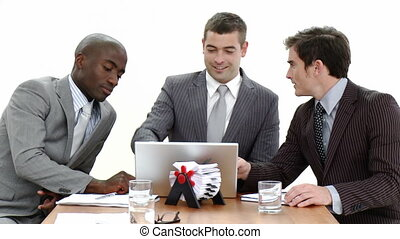 Three businessmen in a meeting using a laptop