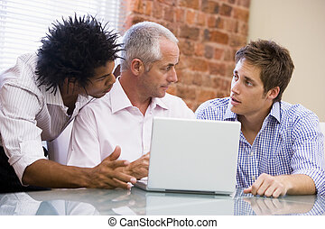 Three businessmen in office with laptop talking