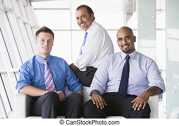 Three businessmen sitting indoors smiling (high key/...