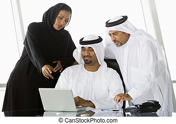 Three businesspeople in office with laptop pointing and ...