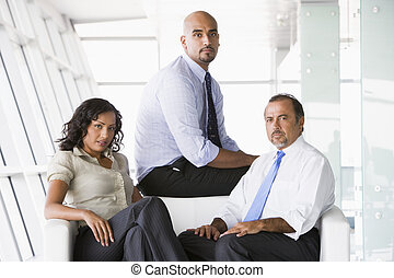 Three businesspeople sitting indoors (high key/selective ...