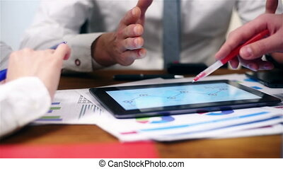 Three Businesspeople Using Touch Pad - Co Worker Using...