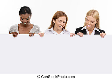 three businesswoman holding white board