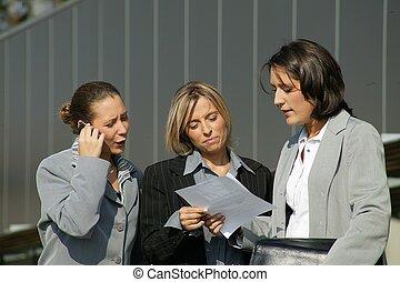 Three businesswoman stood outside office block