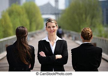 Three businesswomen stood on a bridge