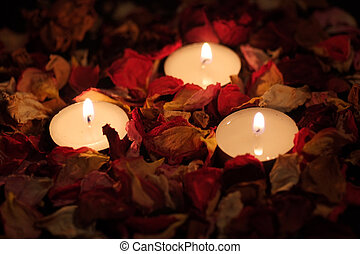 Three candles and dry rose petals