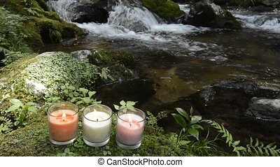 Three candles at riverside - Three glass candles on mossy...