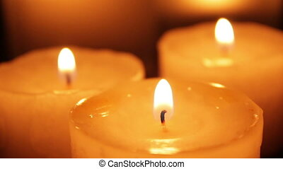 Three candles blazing in the dark