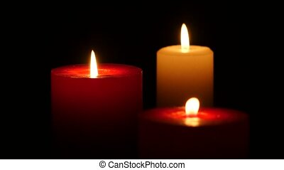 Three candles burning on a black background, Close up -...