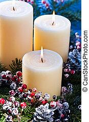 Three candles in an advent flower arrangement