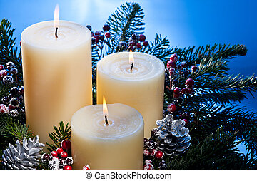 Three candles in an advent flower arrangement for advent and...
