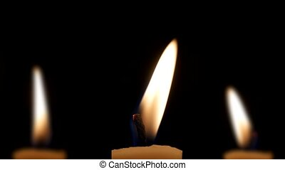 Three candles in dark