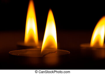 three candles in the dark, close up