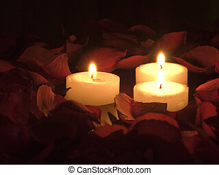 Three Candles - Three burning candles surrounded by rose...