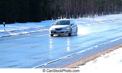 Three cars travelling on a road with snow