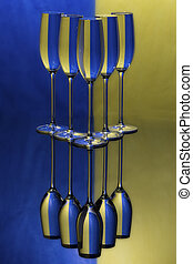 Three champagne glasses on a shiny surface with water that distort yellow and blue background