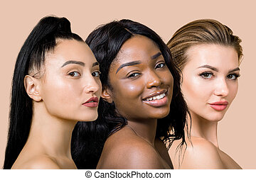 Three charming attractive different ethnicity women, asian, african and caucasian, posing to camera. Beauty skin, face care promotion. Close-up portrait, of girls collage isolated on beige