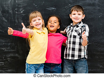 three cheerful children standing together with thumbs up