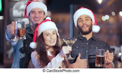 Three cheerful friends in Santa hat with glasses of beer smiling at the camera