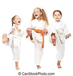 Three cheerful girl on a white background in kimono perform...