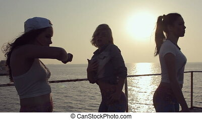 Three cheerful girls dressed in the same leggings dancing at sunset near the sea