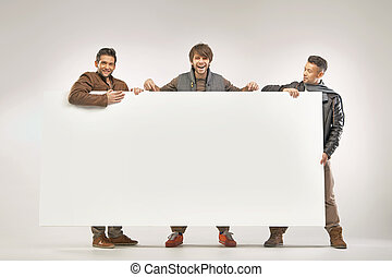 Three cheerful guys holding the board