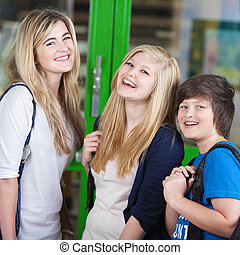 Three cheerful students standing chatting - Three cheerful ...