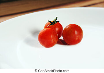 Three cherry tomatoes on white plate