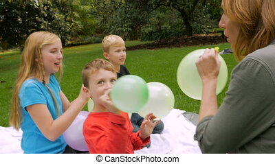 Three children and a mother letting balloons fly away -...