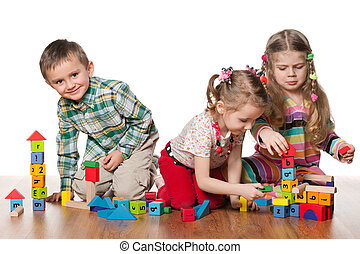Three children are playing on the floor