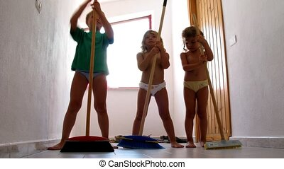 Three children dance with mops, indoor.