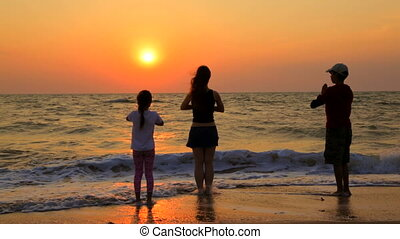 Three Children Doing Yoga Exercises On The Beach At Sunset