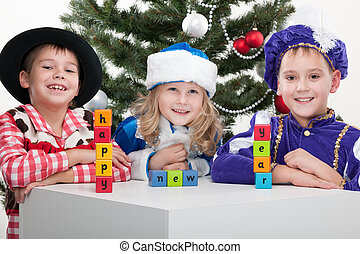 """Three children dressed in carnival suits are greeting with sigh """"happy new year"""" made with blocks at the decorated christmas tree; isolated on the white background"""
