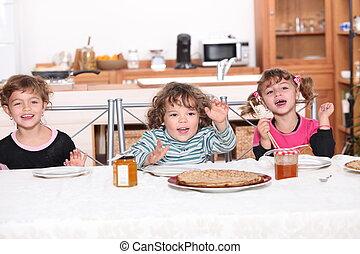 Three children gathered around breakfast table