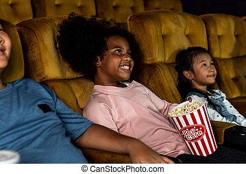 Three children having fun watching movie