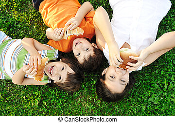 Three children laying on green grass on ground and eating...