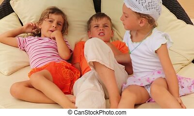 Three children lying on pillows on the bed and talking