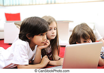 Three children lying with laptop at home on the ground