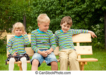 Three children on a bench in identical clothes