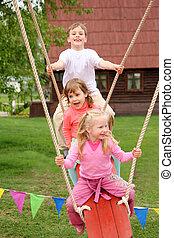 Three children on  swing