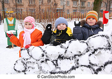 Three children on wall of snow fortress in court yard throw...