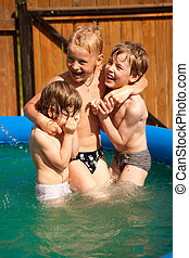 Three children play in inflatable pool
