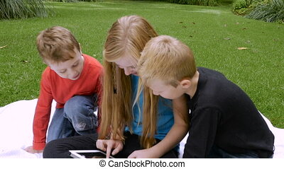 Three children sit on a blanket outside while using a tablet...
