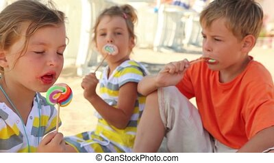 Three children sitting on the sand and eat candy
